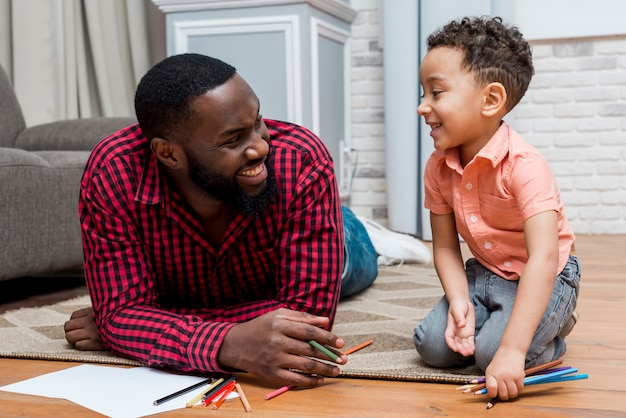 Padre nero e figlio con matite sul pavimento Foto Gratuite