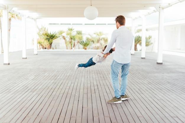 Padre oscillante bambino da braccia sulla spiaggia Foto Gratuite