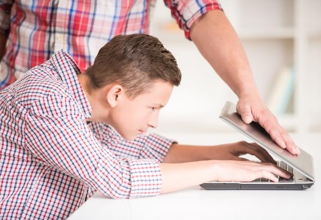 Padre rigoroso che prova a chiudere il computer portatile di suo figlio. Foto Premium