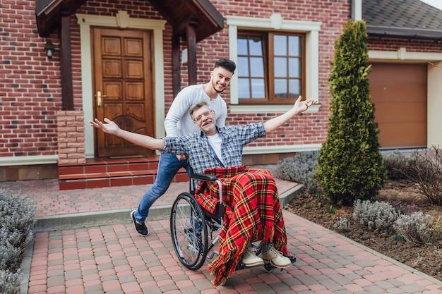 Padre senior in sedia a rotelle e giovane figlio su una passeggiata vicino alla casa di cura. Foto Premium