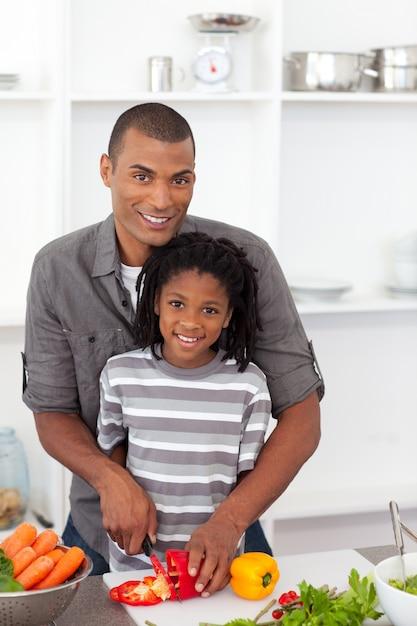 Padre sorridente che aiuta suo figlio a tagliare le verdure Foto Premium