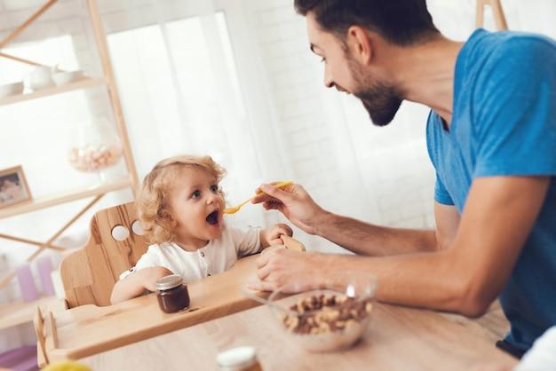 Padre sta dando da mangiare a suo figlio una colazione. Foto Premium