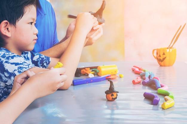 Padre sta giocando a un giocattolo di argilla con un bambino Foto Gratuite
