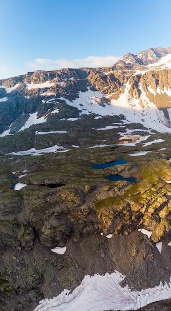 Paesaggio alpino di alta quota con maestose vette rocciose. panorama aereo all'alba. concetto di alpi, ande, himalaya Foto Premium