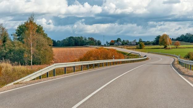 Paesaggio autunnale con strada asfaltata e foresta. Foto Premium