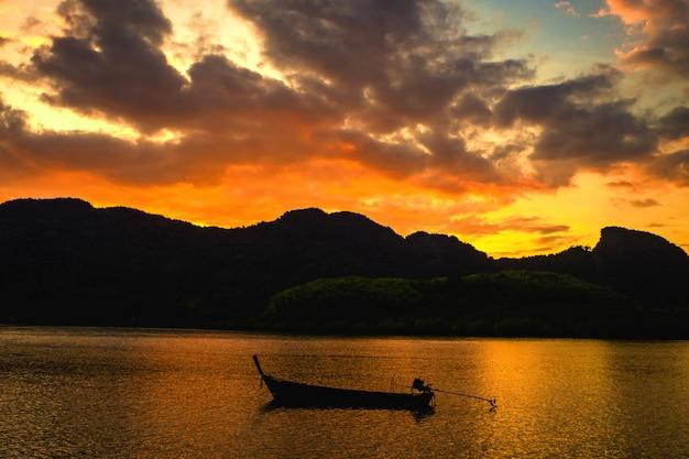 Paesaggio del tramonto, cielo nel tempo crepuscolare con piccoli pescherecci in tailandia Foto Premium
