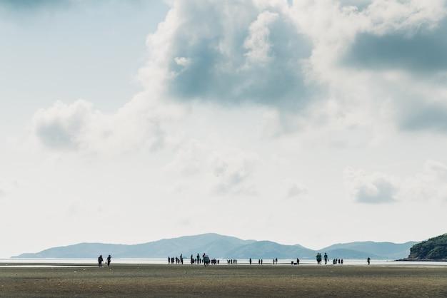 Paesaggio di bassa marea con montagna verde, cielo nuvola con sagome di persone Foto Premium
