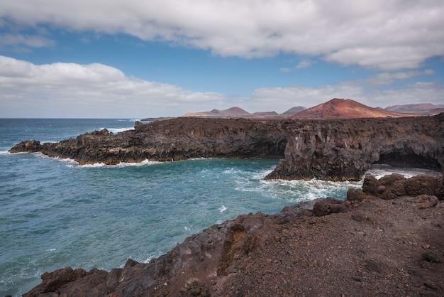 Paesaggio di lanzarote costa di los hervideros, grotte di lava, scogliere e oceano ondulato. Foto Premium