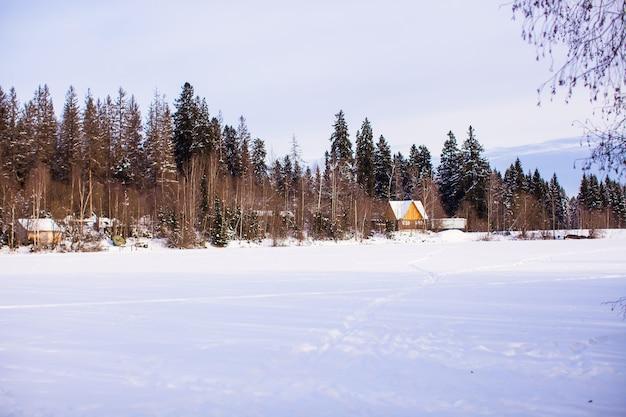 Paesaggio invernale con una piccola casa nella foresta Foto Premium