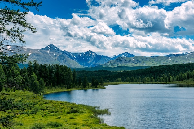 Paesaggio montano, nuvole bianche, lago e catena montuosa in lontananza. Foto Premium