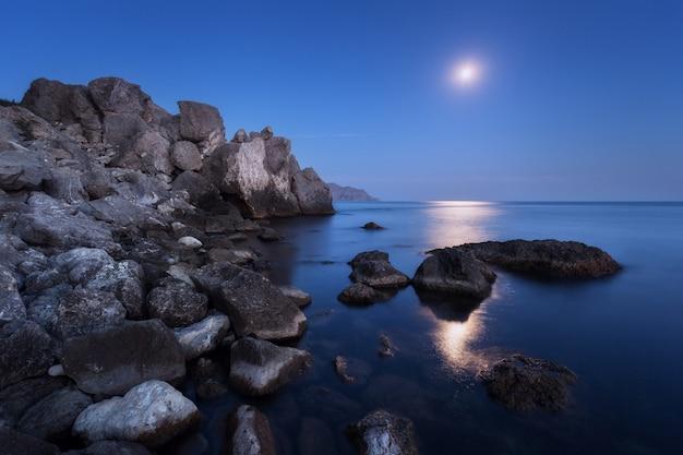 Paesaggio notturno colorato con luna piena, percorso lunare e rocce in estate Foto Premium