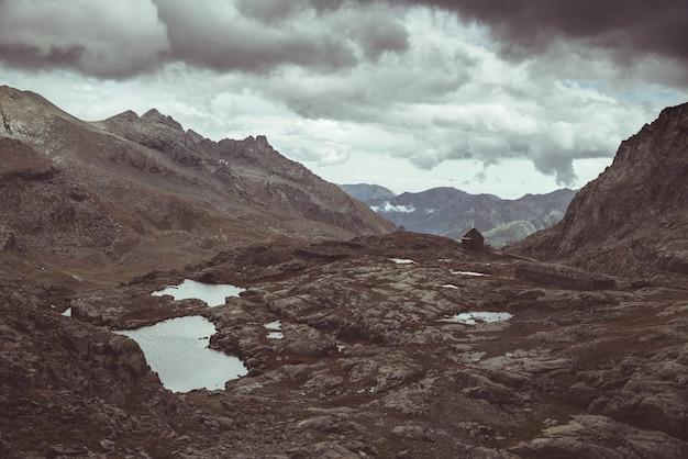Paesaggio roccioso d'alta quota e laghetto. maestoso paesaggio alpino con drammatico cielo tempestoso. vista grandangolare dall'alto, immagine tonica, filtro vintage, tonalità divisa. Foto Premium