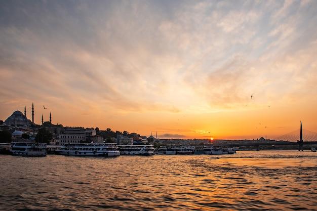 Paesaggio soleggiato di estate a costantinopoli sul tramonto. stretto attraverso il bosforo con vista sulla moschea blu. una nave con i turisti naviga sotto il ponte Foto Premium