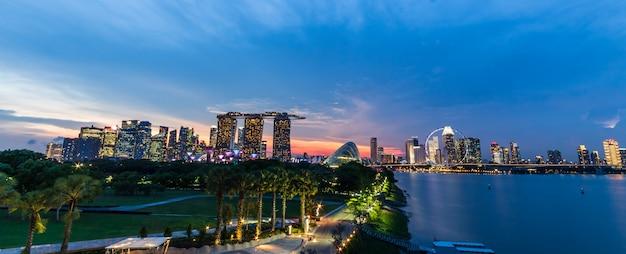 Paesaggio urbano dell'orizzonte di singapore e tramonto sulla baia del porticciolo nel tempo crepuscolare Foto Premium
