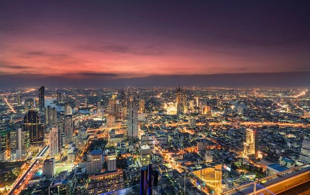 Paesaggio urbano di traffico leggero con il grattacielo e il fiume chao phraya alla metropoli di bangkok Foto Premium