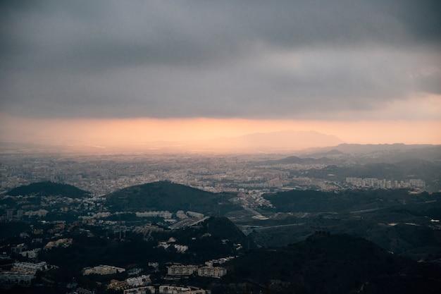 Paesaggio urbano e montagna sotto le nuvole tempestose Foto Gratuite