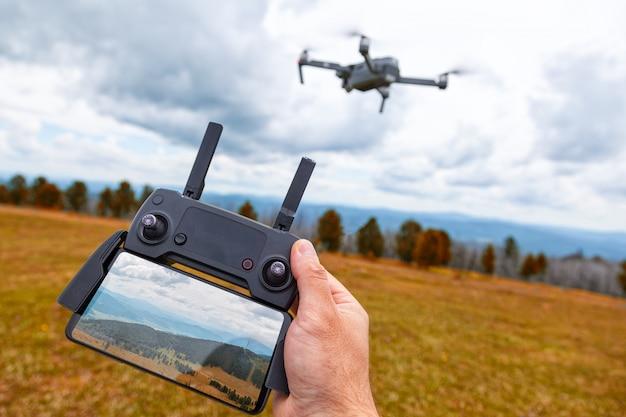 Paesaggistica su un drone. un giovane tiene in mano un pannello di controllo quadricottero con un monitor e un'immagine di montagne Foto Premium