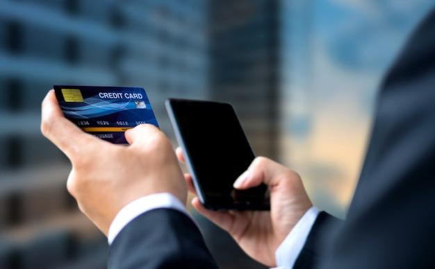 Paga dell'uomo d'affari o acquistando dalla carta di credito con lo smartphone Foto Premium