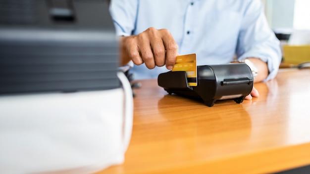 Pagamenti con carta tra uomini d'affari tramite macchina con carta di credito in ufficio. Foto Premium