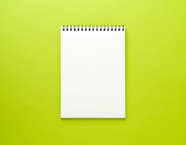 Pagina bianca del blocco note in bianco sullo scrittorio verde, fondo di colore. vista dall'alto, vuota per il testo. Foto Premium