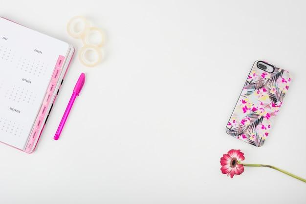 Pagina del calendario; smartphone; fiore; penna e nastro per violoncello su sfondo bianco Foto Gratuite