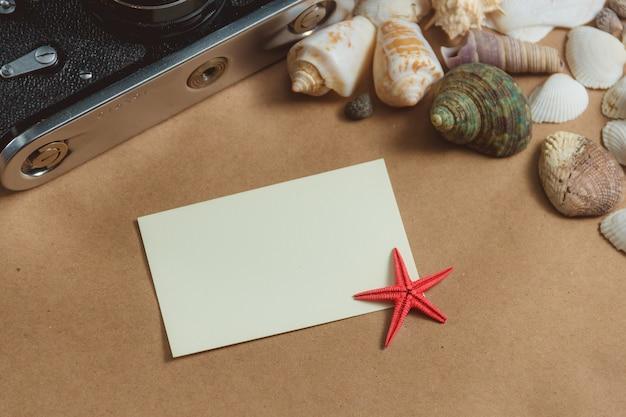 Pagina delle conchiglie e della macchina fotografica della foto su fondo leggero con la carta in bianco Foto Premium