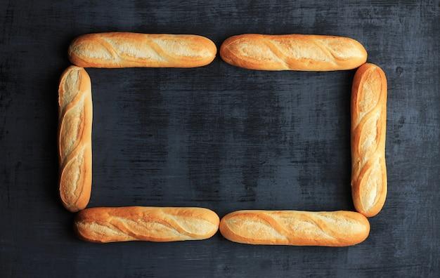 Pagina fatta di sei pagnotte di baguette francesi su fondo di legno nero. Foto Premium