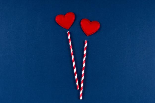 Paglia di carta rossa con cuore su sfondo blu classico colore 2020. san valentino 14 febbraio concetto. vista piana, copia spazio, vista dall'alto. Foto Premium