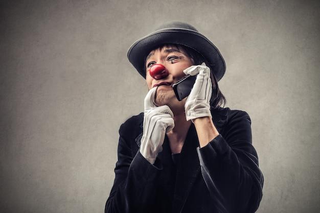 Pagliaccio preoccupato parlando al telefono Foto Premium