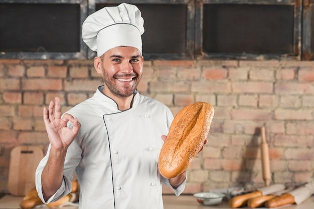 Pagnotta maschio sorridente della tenuta del panettiere che mostra gesto giusto del segno della mano Foto Gratuite