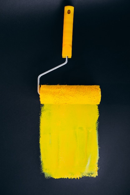 Paintroller per riparazioni isolato su sfondo nero in vernici gialle Foto Gratuite