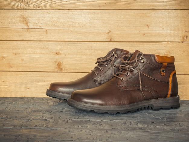 Paio di scarpe classiche da uomo marroni sulle pareti in legno del pavimento scuro. il concetto di scarpe da uomo casual. Foto Premium