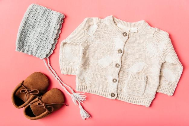 Paio di scarpe di lana; berretto e vestiti del bambino su sfondo di pesca Foto Gratuite