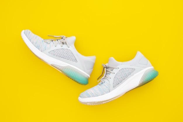 Paio di sneakers sportive alla moda su sfondo giallo. Foto Premium