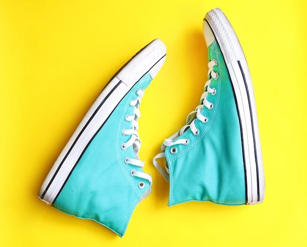 Paio di vecchie scarpe da tennis blu isolato su giallo Foto Premium