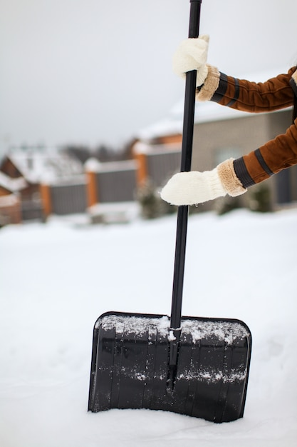 Pala da neve in mani femminili in una giornata invernale Foto Premium