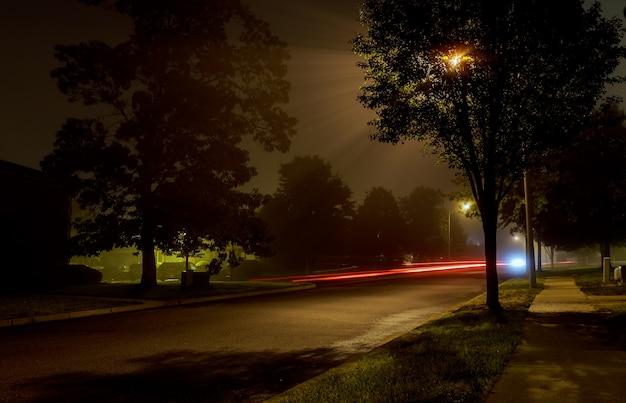 Palazzina di appartamenti sulla strada della città di notte vuota coperto di nebbia Foto Premium