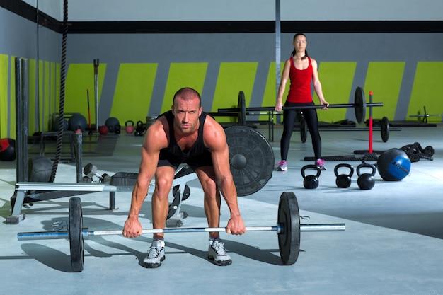 Palestra con sollevamento pesi bar allenamento uomo e donna Foto Premium