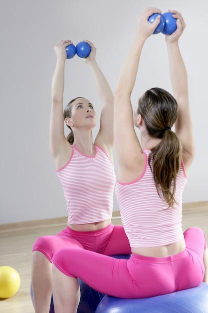 Palestra di sport delle palle di tonalità della donna della palestra dei pilates dello specchio Foto Premium
