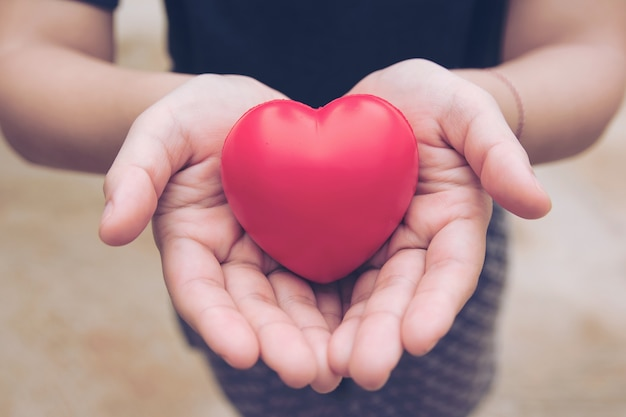 Palla cuore rosso: palla antistress in schiuma a forma di cuore rosso sulla mano della donna. regalo san valentino Foto Premium