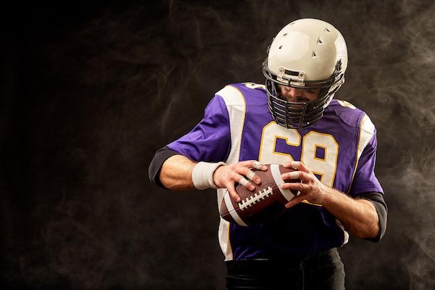 Palla della tenuta del giocatore di football americano in sue mani Foto Premium