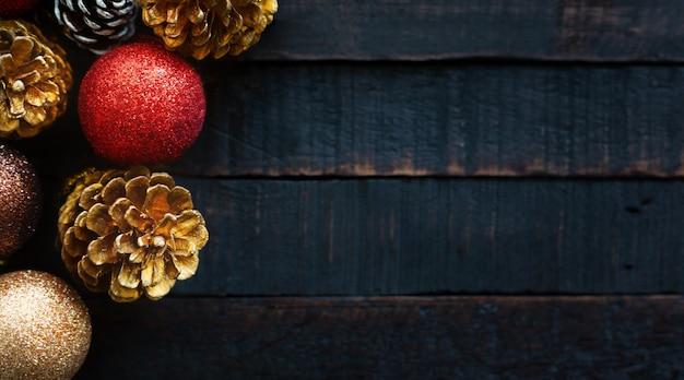 Palle della decorazione di natale e della pigna su fondo di legno scuro. Foto Premium
