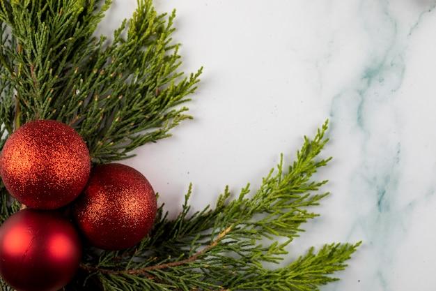 Palle rosse dell'albero di natale su un ramo verde nell'angolo. Foto Gratuite