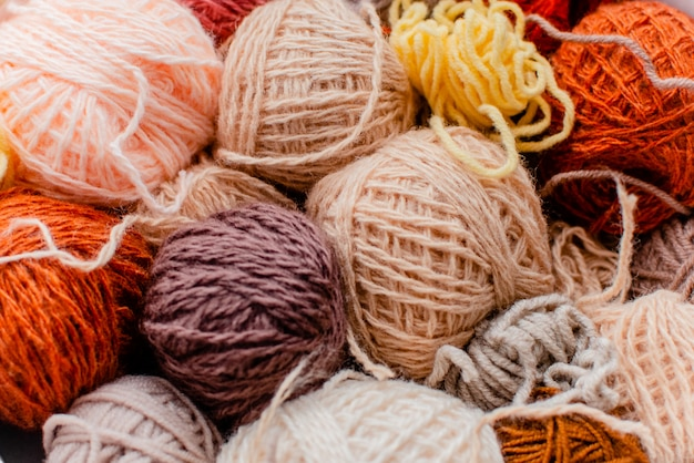 Palle variopinte di lana con i ferri da maglia su fondo bianco, sul hobby e sul concetto di tempo libero. filati per maglieria Foto Premium