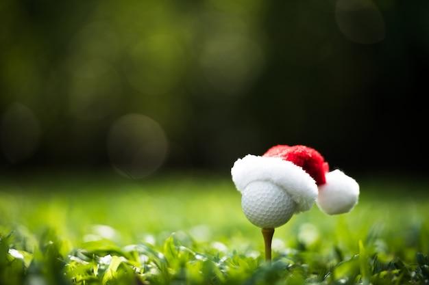Pallina da golf dall'aspetto festivo sul tee con il cappello di babbo natale in cima per le festività natalizie sul campo da golf Foto Premium