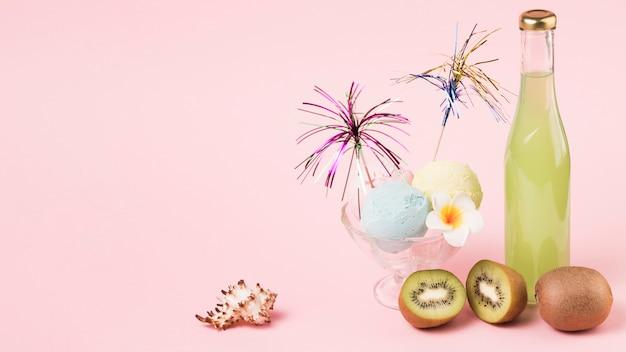 Palline di gelato con la bacchetta ornamentale sulla ciotola di vetro vicino a frutta e bottiglia Foto Gratuite