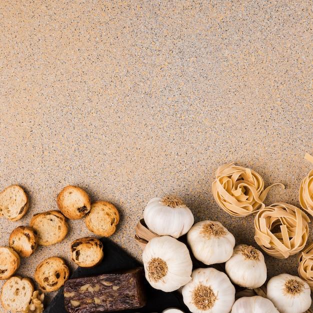 Palline di pasta cruda; bulbi d'aglio; fette di pane e formaggio marrone disposte sul fondo della carta da parati Foto Gratuite