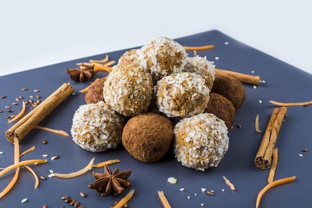 Palline proteiche energetiche con carote, noci, scaglie di cocco e tartufi di cioccolato vegani Foto Premium