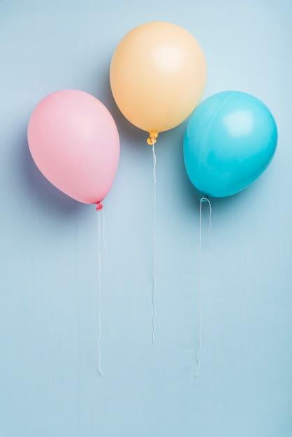 Palloncini colorati su sfondo blu con spazio di copia Foto Gratuite