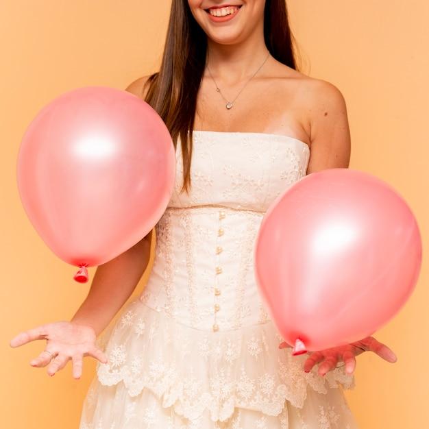 Palloncini di compleanno della holding dell'adolescente di vista frontale Foto Gratuite